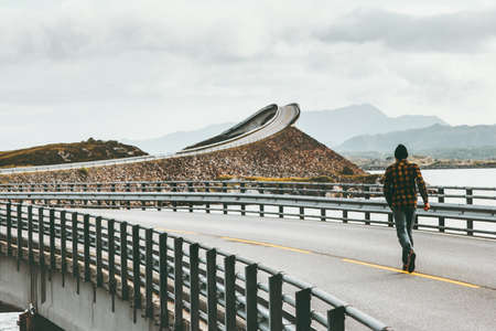 Man running away at Atlantic road in Norway Storseisundet bridge Travel Lifestyle concept adventure vacations outdoor