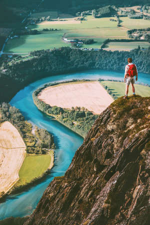 Man adventurer with backpack on cliff Travel lifestyle concept active weekend summer vacations tourist enjoying river aerial view