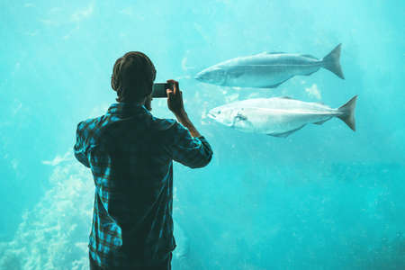 Man taking photo by smartphone of fish in big aquarium Travel Lifestyle concept modern technology
