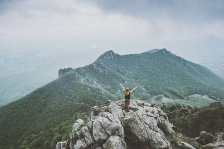 Happy woman standing on mountain summit hands raised Travel Lifestyle success motivation concept adventure active vacations outdoor aerial view foggy landscape on background Banque d'images