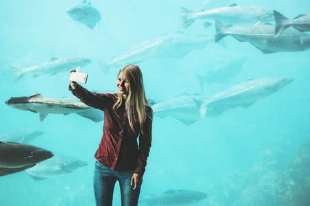 Woman taking selfie by smartphone at big aquarium fish Travel Lifestyle concept modern technology Banque d'images