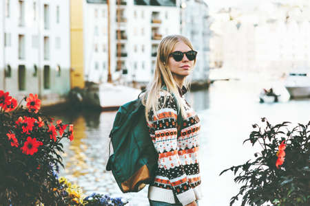 Young woman with backpack sightseeing walk in Alesund city Norway vacations weekend Travel Lifestyle fashion outdoor  Stock Photo