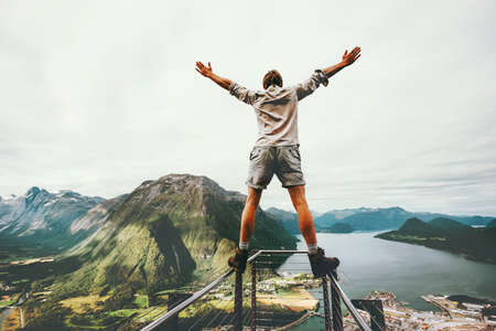Man raised hands balancing at the edge cliff Rampestreken landmark in Norway mountains Travel lifestyle risk concept active vacations happy tourist enjoying landscape aerial view Stock Photo