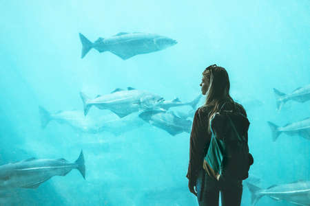 Woman tourist watching for fish in big aquarium Travel Lifestyle concept