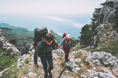 Couple Man and Woman holding hands hiking in mountains Love and Travel Lifestyle concept. Backpackers family traveling together active adventure vacations Banque d'images