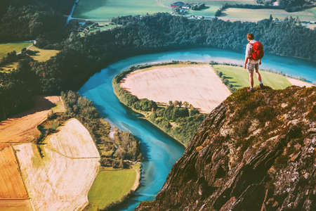 Travel Man on mountains cliff edge with backpack Adventure lifestyle concept active weekend summer vacations river aerial view