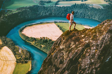 Hiking adventure in Norway mountains Man with backpack on cliff Travel lifestyle concept active weekend summer vacations river aerial view