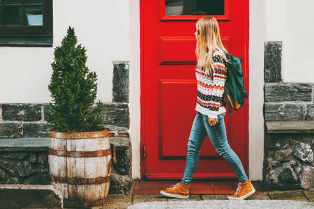 Young woman with backpack walking in city red door house on background Travel Lifestyle concept vacations Banque d'images