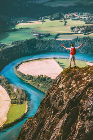 Happy Man traveler standing on cliff mountain hands raised Travel Lifestyle success motivation concept adventure active vacations outdoor river aerial view
