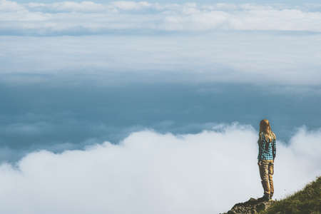Woman standing on cliff above clouds mountains Travel Lifestyle adventure emotional concept  vacations outdoor