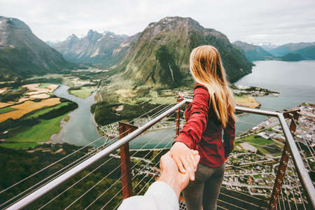 Couple Man and Woman follow holding hands in Norway mountains Love and Travel happy emotions Lifestyle concept. Young family traveling active adventure vacations Rampestreken aerial view