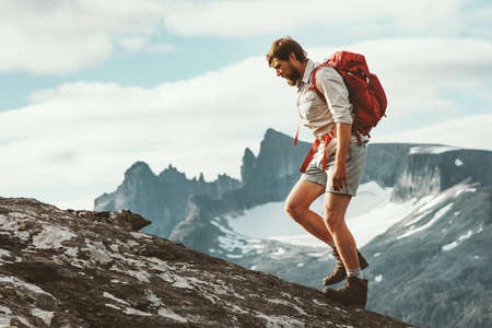 Man hiking in mountains with backpack Travel sport lifestyle concept active weekend summer vacations wild trek