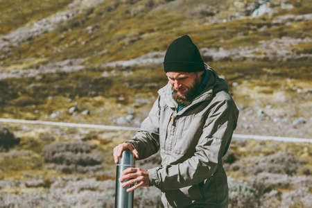 Man traveler holding thermos survival in mountains Travel lifestyle concept into the wild vacations