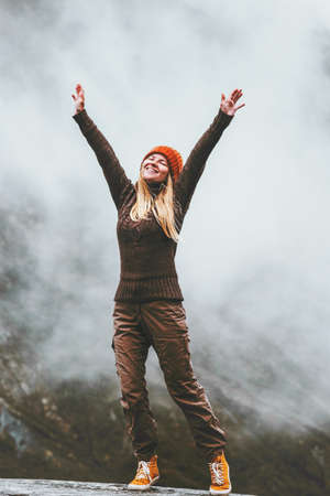 Happy woman in foggy mountains Travel Lifestyle success motivation concept adventure active vacations outdoor blessing emotions raised hands