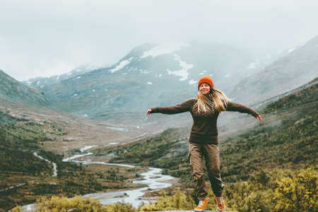 Woman bliss emotional raised hands foggy mountains on background Travel Lifestyle wellness concept adventure  vacations outdoor harmony with nature Jotunheimen park in Norway 스톡 콘텐츠