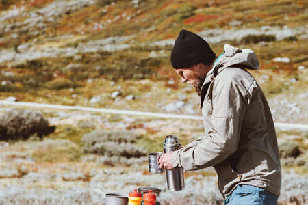 Man traveler holding cup and thermos cooking in mountains Travel lifestyle survival concept vacations oudoor into the wild