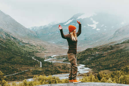 Woman walking outdoor happy emotions foggy mountains on background Travel Lifestyle success concept adventure active vacations in Norway Jotunheimen park