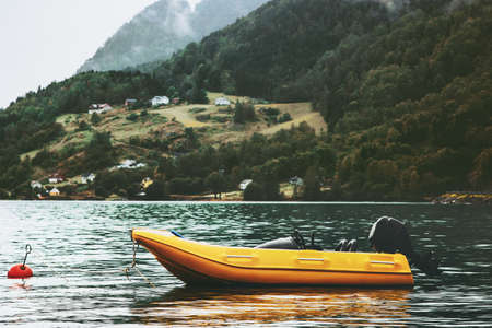 Yellow boat fjord and foggy Mountains Landscape in Norway Travel scenic view Stock Photo