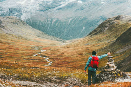 Man placing stone to rock cairn marking route hiking in mountains with backpack Travel healthy lifestyle concept active  vacations wild trek in Scandinavia Stock Photo