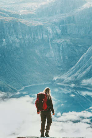 Hiker woman with backpack above clouds and lake in mountains Travel Lifestyle wanderlust concept adventure active vacations outdoor hiking sport