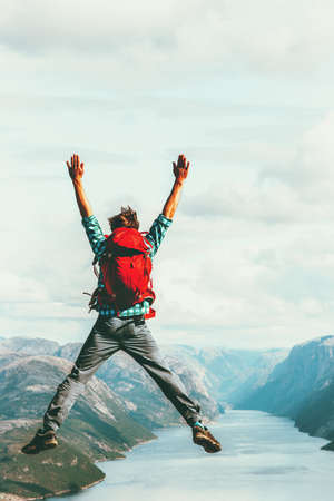 Happy Man extreme jumping Travel Lifestyle adventure concept active summer vacations with backpack outdoor success euphoria emotions in Norway above Lysefjord cliff