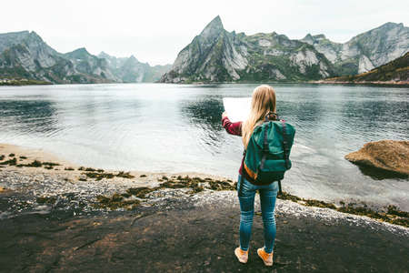 Woman with map and backpack planning route sightseeing Lofoten islands in Norway solo travel lifestyle concept adventure outdoor summer vacations  스톡 콘텐츠