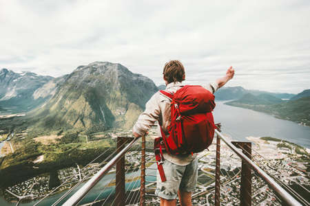 Traveler man raised hand showing mountains Travel Lifestyle adventure summer vacations success happy emotions in Norway backpacker on Rampestreken viewpoint  Stock Photo