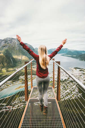 Happy woman raised hands enjoying mountains landscape Travel Lifestyle adventure vacations success emotions in Norway Rampestreken viewpoint