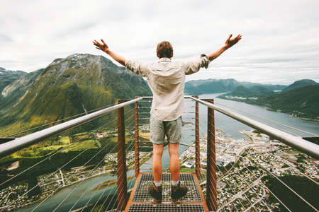 Happy tourist man raised hands enjoying aerial mountains landscape Travel healthy Lifestyle adventure vacations success emotions traveler standing alone on Rampestreken viewpoint in Norway