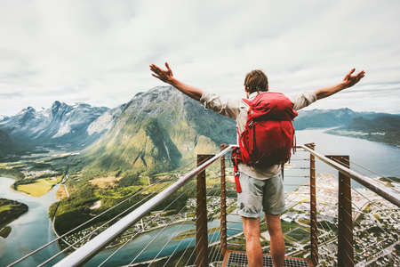 Happy man raised hands enjoying aerial mountains landscape Travel Lifestyle adventure vacations success emotions in Norway traveler with backpack standing alone on Rampestreken viewpoint in Norway