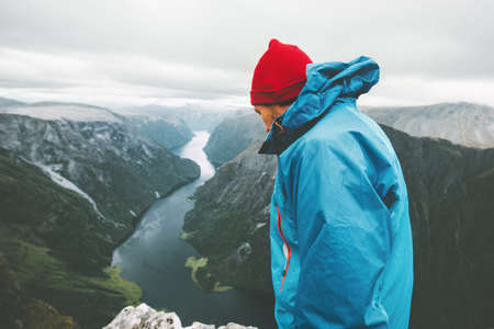 Man traveler on mountain top standing alone traveling in Norway Lifestyle adventure active vacations aerial fjord view moody scandinavian weather