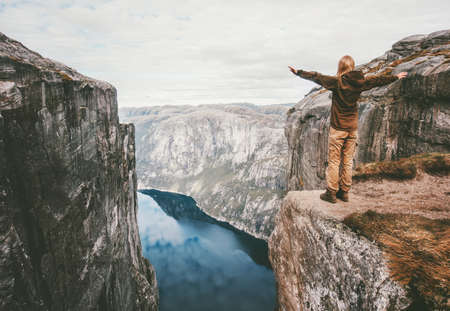 Traveling woman standing on cliff over fjord alone raised hands hike in Norway adventure lifestyle weekend getaway trip Kjerag rocky mountains Stock Photo