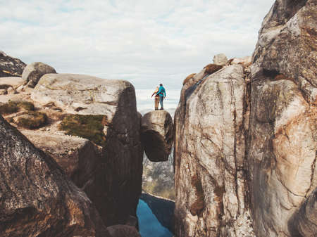 Travel couple on Kjeragbolten romantic trip in Norway Kjerag mountains vacations adventure lifestyle family man and woman together extreme journey