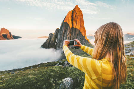 Woman tourist taking photo by smartphone sightseeing sunset Segla mountain in Norway adventure journey summer vacations traveling lifestyle