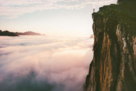 Traveler standing on cliff edge mountain top above sunset clouds travel adventure lifestyle summer journey vacations Imagens