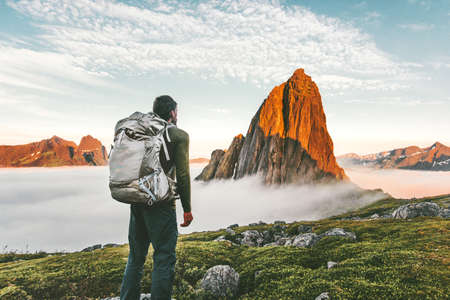 Backpacker man exploring sunset rocky mountains alone hiking adventure journey summer vacations traveling lifestyle weekend getaway Imagens