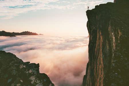 Reisender Mann, der auf der Randklippe über Wolkensonnenuntergangsgebirgen steht, reist Abenteuer-Lifestyle-Reiseurlaub in Norwegen