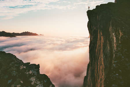 Viaggiatore uomo in piedi sul bordo scogliera sopra le nuvole tramonto montagne viaggio avventura stile di vita vacanze viaggio in Norvegia