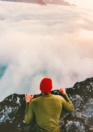 Man on the edge cliff above clouds gaze into abyss lying down mountains travel adventure lifestyle extreme vacations