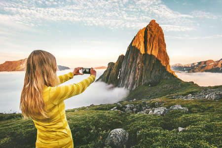 Woman traveler taking photo by smartphone exploring sunset rocky mountains in Norway adventure journey summer vacations traveling lifestyle Imagens