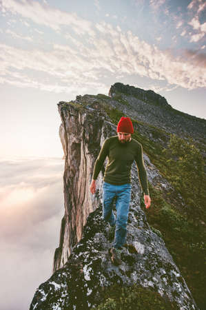 Man walking alone on the edge mountain ridge above clouds travel adventure lifestyle extreme hiking vacations