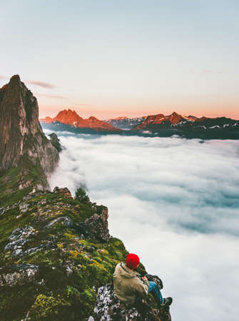 Outdoor adventure Man relaxing alone on cliff edge mountains above clouds sea travel lifestyle extreme vacations in Norway Segla mountain