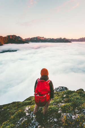 Traveler with backpack hiking over clouds alone traveling in mountains adventure lifestyle epic journey vacations Imagens