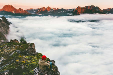 Man relaxing alone on cliff edge mountains above clouds sea travel adventure lifestyle extreme vacations in Norway