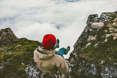 Man relaxing sitting alone on cliff edge rocky mountains above clouds travel adventure lifestyle extreme vacations