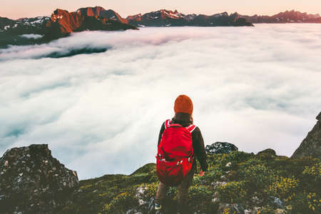 Adventurer backpacker on cliff over clouds in sunset mountains alone hiking adventure journey outdoor vacations traveling lifestyle weekend getaway