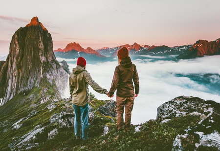 Couple adventurers hands holding  traveling in Norway mountains healthy lifestyle concept active vacations outdoor hiking Segla together enjoying sunset landscape Imagens