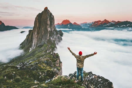 Traveler enjoying sunset Segla mountain hiking adventure outdoor in Norway active vacations traveling lifestyle man raised hands on cliff above clouds Imagens