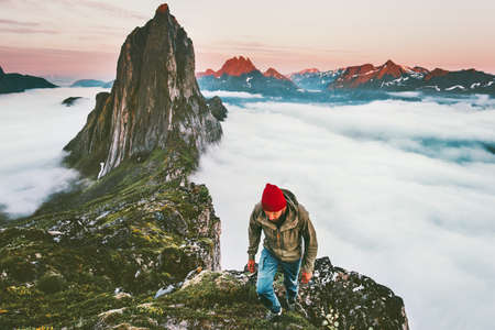Adventurous man hiking in mountains  outdoor active lifestyle travel vacations sunset Segla peak above clouds in Norway Imagens
