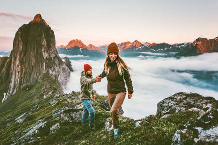 Coppia felice mano nella mano che viaggiano insieme escursioni in Norvegia concetto di stile di vita sano vacanze attive all'aperto Segla montagna tramonto paesaggio